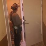 Här håller vi på att montera in säkrare dörrar och lås. Vi tar bort de gamla dörrarna och passar in de nya dörrarna och förser dem med riktiga lås. Här är Leif i farten