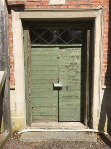 Låskåpa på grön äldre dörr